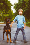 Blonde boy posing with the dog or doberman in Royalty Free Stock Photo