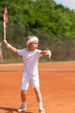 Blonde boy practicing tennis Royalty Free Stock Photography