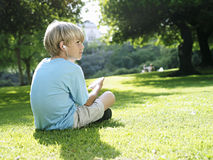 Blonde boy (7-9) sitting on grass in park, listening to MP3 player, side view Stock Photo