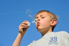 Blonde boy with soap bubbles Stock Images