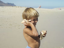 Blonde boy (5-7) standing on beach, listening to sea shells, smiling, side view royalty free stock photography