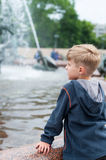Blonde boy standing at a fountain Royalty Free Stock Photos