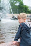 Blonde boy standing at a fountain Stock Photos