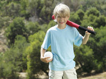 Blonde boy (7-9) standing in park with softball bat and ball, smiling, front view, portrait Royalty Free Stock Images