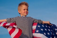 Free Blonde Boy Waving National USA Flag Outdoors Over Blue Sky At Summer - American Flag, Country, Patriotism, Independence Stock Image - 186099031