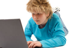 Blonde boy working with laptop stock image
