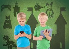 Blonde boys with tablet and phone in front of green background with toys graphics. Digital composite of Blonde boys with tablet and phone in front of green Stock Photography