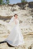 Blonde Braut auf einem Sand im weißen Kleid Lizenzfreie Stockfotos