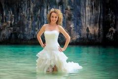 Blonde Braut der Nahaufnahme in den flaumigen Händen auf Taille im flachen Meer Lizenzfreies Stockfoto