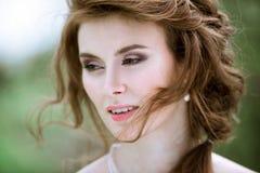 Blonde Braut der Nahaufnahme mit Modehochzeitsfrisur und -make-up Stockfotografie