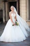 Blonde Braut der schönen Märchen, die mit Blumenstrauß in altem ital aufwirft Lizenzfreie Stockbilder