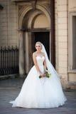 Blonde Braut der schönen Märchen, die mit Blumenstrauß in altem ital aufwirft Stockfoto
