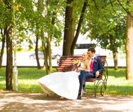Blonde Braut der stilvollen Hochzeitspaare im weißen Kleid und eleganten im Bräutigam, die auf einer Bank im Park sitzt Stockbild