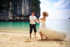 blonde Braut des Bräutigams im flaumigen Kleid schließen sich Händen schwingen auf Strand an Stockfotografie