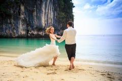 blonde Braut des Bräutigams im flaumigen Kleid schließen sich Händen schwingen auf Strand an Stockfotos