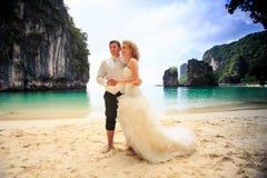 Blonde Braut des Nahaufnahmebräutigams im flaumigen Stand schließen sich Händen auf Strand an Stockfotografie