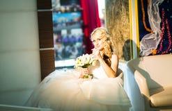 Blonde Braut, die auf dem Lehnsessel im Raum sitzt Lizenzfreies Stockfoto