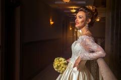 Blonde Braut, die beiseite im Hochzeitskleid lächelt und schaut Lizenzfreies Stockfoto