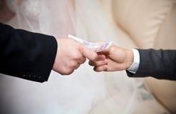 Blonde Braut, die Boutonniere auf Bräutigamjacke justiert Stockbild