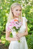 Blonde Braut, die den Blumenstrauß lächelt an der Kamera hält Stockfotos