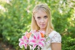 Blonde Braut, die den bunten Blumenstrauß betrachtet Kamera hält Lizenzfreie Stockfotografie