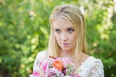 Blonde Braut, die den bunten Blumenstrauß weg schaut hält Stockfotografie