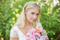 Blonde Braut, die den großen Blumenstrauß lächelt an der Kamera hält Lizenzfreie Stockbilder