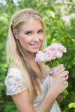 Blonde Braut, die den rosa Blumenstrauß lächelt an der Kamera hält Stockfotos