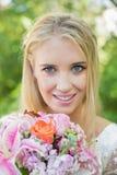 Blonde Braut, die an der Kamera hält Blumenstrauß lächelt Lizenzfreies Stockbild