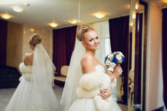 Blonde Braut, die in einem Hochzeitskleid im interrior nahe Spiegel aufwirft Stockfotos