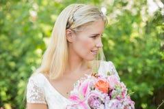 Blonde Braut, die großen Blumenstrauß hält Lizenzfreies Stockfoto
