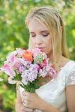 Blonde Braut, die ihren bunten Blumenstrauß riecht Lizenzfreies Stockbild