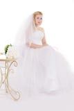 Blonde Braut, die mit Blumenstrauß sitzt Stockfoto