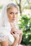 Blonde Braut in einem Schleier, der ihre Hände zu ihrem Kasten hält Stockfoto