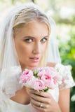 Blonde Braut in einem Schleier, der sie rosafarbener Blumenstrauß hält Lizenzfreies Stockbild