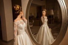 Blonde Braut im Hochzeitskleid, das den Spiegel betrachtet Stockfotografie