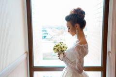 Blonde Braut im Hochzeitskleid mit Blumenstrauß von Rosen in den Händen Lizenzfreie Stockfotografie