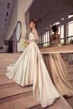 Blonde Braut im Hochzeitskleid mit Blumenstrauß von Rosen in ihren Händen Lizenzfreie Stockbilder