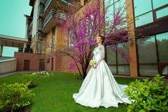 Blonde Braut im Hochzeitskleid und -rosen in ihren Händen, die mit Kirschblüte-Baum auf Hintergrund aufwerfen Lizenzfreie Stockfotografie