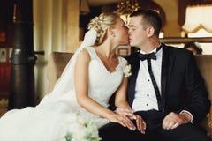 Blonde Braut küsst einen Bräutigam, der mit ihm auf einem Sofa in einer Halle sitzt Lizenzfreies Stockfoto