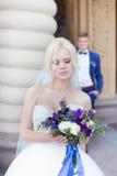 Blonde Braut mit Blumenstrauß in der Hand, im Hintergrund in einer blauen Klage Stockfoto