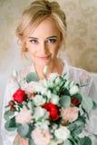 Blonde Braut mit dem Haar steht oben mit rotem Blumenstrauß Lizenzfreie Stockfotografie