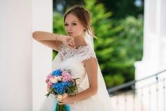 Blonde Braut mit den blauen Augen, die im Hochzeitskleid mit Blumenstrauß von Blumen aufwerfen Das Modell hob ihre Hand zu ihrem  Stockfotografie