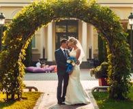 blonde Braut mit einem Blumenstrauß von Blumen in ihren Händen und ihr Verlobtes stehen nahe einem natürlichen Bogen Lizenzfreie Stockfotos