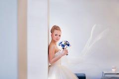 Blonde Braut mit einem Schleier auf weißem Innenraum mit Kopienraum Stockfotografie