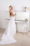 Blonde Braut nahe dem Klavier Lizenzfreie Stockbilder