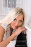 Blonde Braut nahe dem Klavier Lizenzfreie Stockfotografie