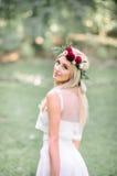 Blonde Braut schaut über ihrer zarten Schulter bei der Aufstellung Lizenzfreies Stockbild