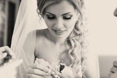 Blonde Braut schaut auf Blumen Stockfoto