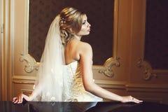 Blonde Braut schaut die herrliche Aufstellung hinter einem Fenster Stockbilder